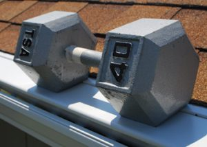 An image of a 40-pound dumbbell sitting on a LeaFree gutter guard to display it's strength.